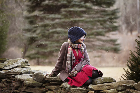 Happy woman looking away while relaxing on stone wall - CAVF10065