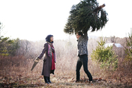 Man carrying pine tree while woman holding saw against clear sky - CAVF10068