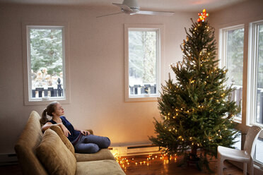 Woman looking at Christmas tree while sitting on sofa - CAVF10077