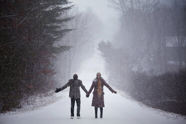 Couple holding hands while standing on snowy field during winter - CAVF10083