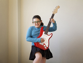 Cheerful girl playing guitar against wall at home - CAVF10104