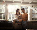 Happy couple by kitchen counter at home - CAVF10125