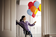 Happy woman standing by staircase while holding helium balloons - CAVF10143