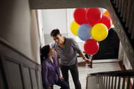 High angle view of man holding helium balloons while standing by woman at home - CAVF10146