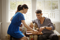 Couple playing Backgammon while sitting on armchair at home - CAVF10149