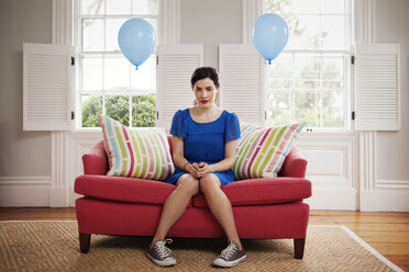 Portrait of woman sitting on sofa by helium balloons at home - CAVF10152