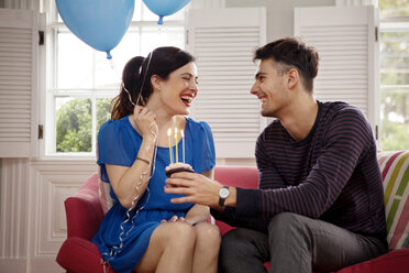 Happy couple celebrating birthday while sitting on sofa at home - CAVF10155