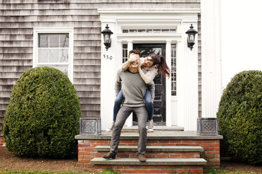 Man giving piggyback to woman while standing on front stoop - CAVF10158