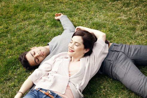 High angle view of happy couple lying on grass at park - CAVF10161