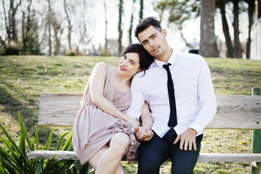 Portrait of happy couple sitting on bench at park - CAVF10179