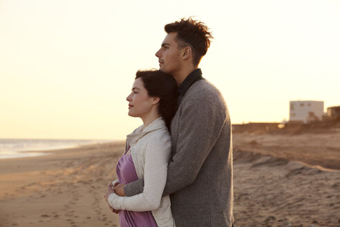 Couple looking at view while standing at beach against clear sky - CAVF10182