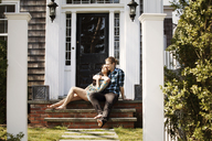 Couple sitting on front stoop - CAVF10203