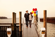 Woman holding helium balloons while walking with man on pier during sunset - CAVF10215