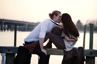 Romantic couple kissing while sitting on railing against sky - CAVF10218