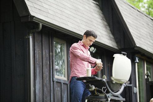 Man preparing food on barbecue grill - CAVF10293