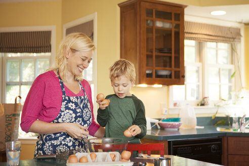 Happy mother and son preparing food in kitchen at home - CAVF10320