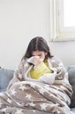 Girl having a cold sitting on the couch at home blowing nose - LVF06789