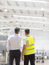 Supervisor and worker talking in warehouse - CAIF19563