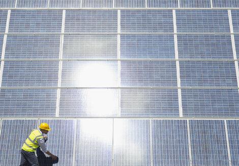 Worker examining solar panels - CAIF19629