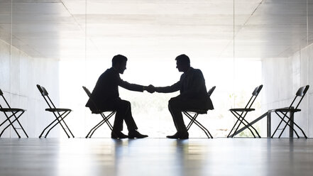 Businessmen shaking hands in office - CAIF19671
