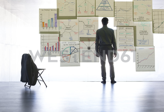 Businessman looking at graphs and charts on glass wall in office - CAIF19674