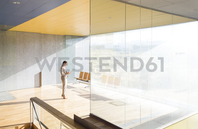 Businesswoman standing in sunny office - CAIF19677