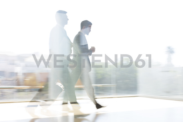 Businessmen walking in sunny airport corridor - CAIF19680