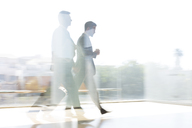 Businessmen walking in sunny airport corridor - CAIF19680