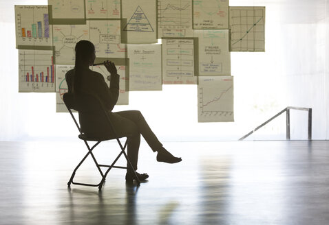 Businesswoman studying charts and graphs on wall in office - CAIF19686