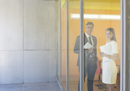 Business people smiling at office window - CAIF19689