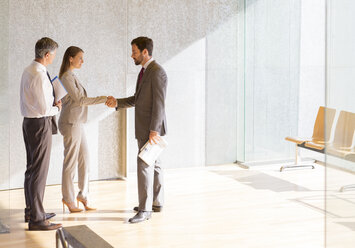 Business people shaking hands in sunny office lobby - CAIF19692
