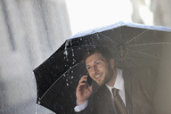 Businessman talking on cell phone under umbrella in rain - CAIF19707