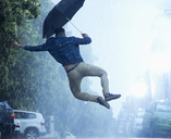 Man with umbrella jumping in rain - CAIF19728