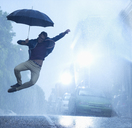 Enthusiastic man with umbrella jumping in rain - CAIF19731