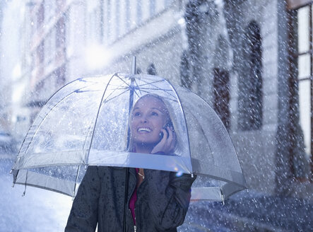 Smiling businesswoman talking on cell phone under umbrella in rainy street - CAIF19749