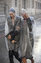 Businesswomen in ponchos walking in rainy street - CAIF19755