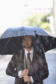 Businessman under umbrella in rain - CAIF19779