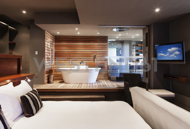 Bed and bathtub in modern master bedroom - CAIF19857