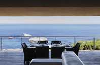 Dining table on luxury balcony overlooking ocean - CAIF19869