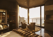 Luxury bedroom overlooking ocean at sunset - CAIF19878