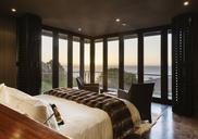 Luxury bedroom overlooking ocean at sunset - CAIF19884
