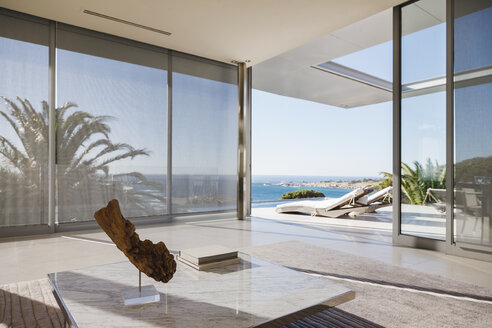 Modern living room and patio overlooking ocean - CAIF19956