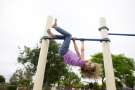 Playful girl hanging upside down on monkey bars at playground against clear sky - CAVF10371