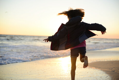 Rear view of playful girl running on shore against clear sky during sunset - CAVF10416
