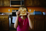 Girl holding bread against her face in kitchen - CAVF10419