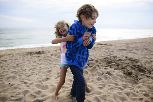 Playful sister tickling brother while standing at Huntington Beach against sky - CAVF10440