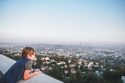 High angle view of boy looking at cityscape while leaning on retaining wall against sky at terrace - CAVF10473