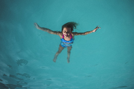 High angle view of carefree girl floating on water in swimming pool - CAVF10476