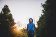 Happy boy wearing hooded jacket while standing by pine trees on field against clear sky during sunset - CAVF10479