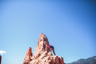 Low angle view of girl climbing on rock formation against sky - CAVF10488